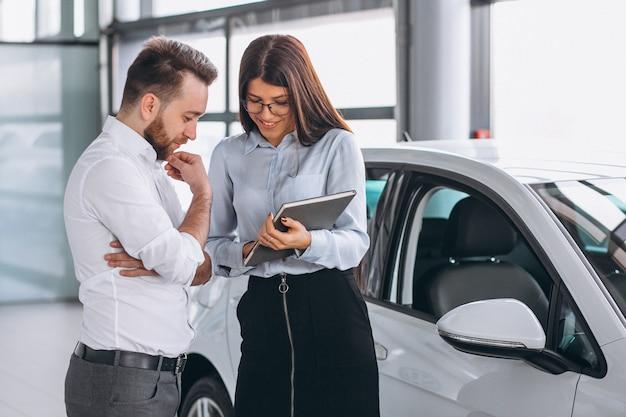 Verkäufer und frau, die nach einem auto in einem autosalon suchen Kostenlose Fotos