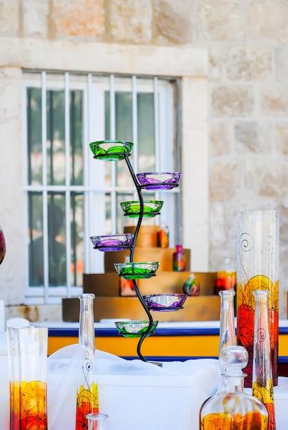 Verkäufer verkaufen auf dem stadtmarkt eine vielzahl von glaswaren, die in verschiedenen farben lackiert sind. Premium Fotos