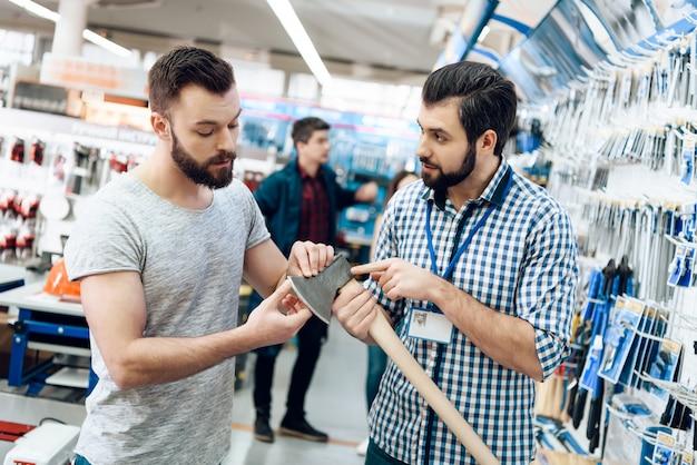 Verkäufer zeigt dem kunden neue axt im geschäft. Premium Fotos