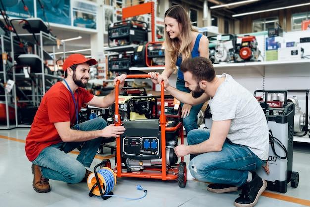 Verkäufer zeigt einigen kunden neuen generator. Premium Fotos