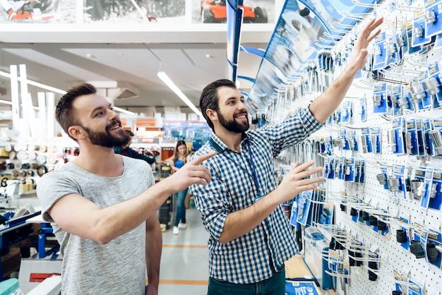 Verkäufer zeigt kundenauswahl der ausrüstung. Premium Fotos
