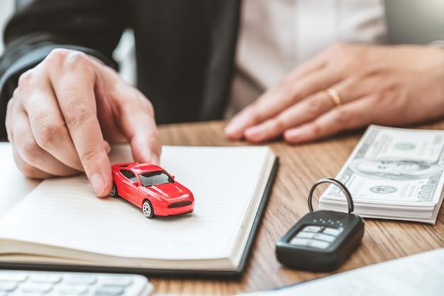 Verkaufsagent, der dem kunden auto gibt und vereinbarungsvertrag, versicherungsauto unterzeichnet. Premium Fotos
