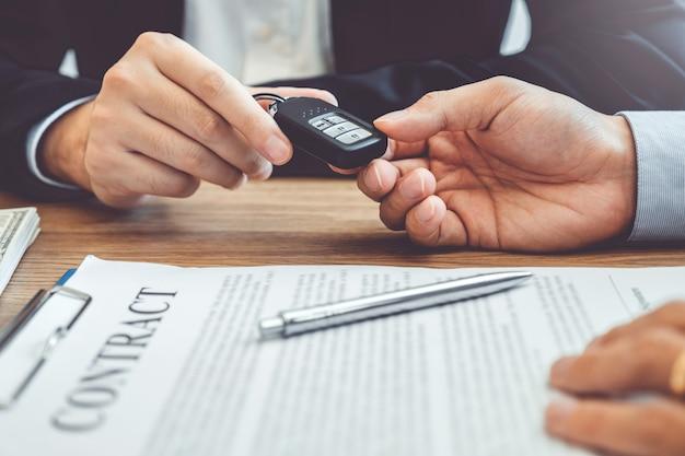 Verkaufsagent, der dem kunden autoschlüssel gibt und vereinbarungsvertrag, versicherungsauto unterzeichnet. Premium Fotos