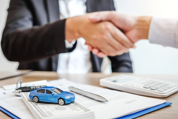 Verkaufsagentenhändedruckabkommen, zum des erfolgreichen autokreditvertrags mit kunden zu vereinbaren und des vertrags zu unterzeichnen versicherungsautokonzept. Premium Fotos