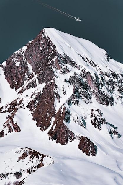 Verkehrsflugzeug mit kondensstreifen über dem schneebedeckten berggipfel Kostenlose Fotos