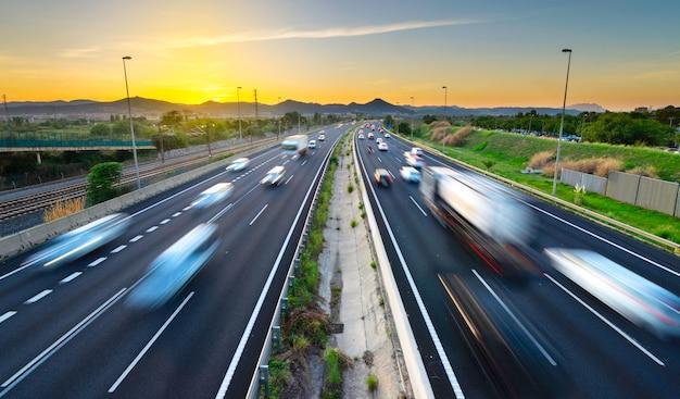 Verkehrsreiche landstraße bei sonnenuntergang, kommende und gehende fahrzeuge, stadtdruck Premium Fotos