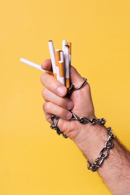 Verkettete hand, die zigaretten hält Kostenlose Fotos