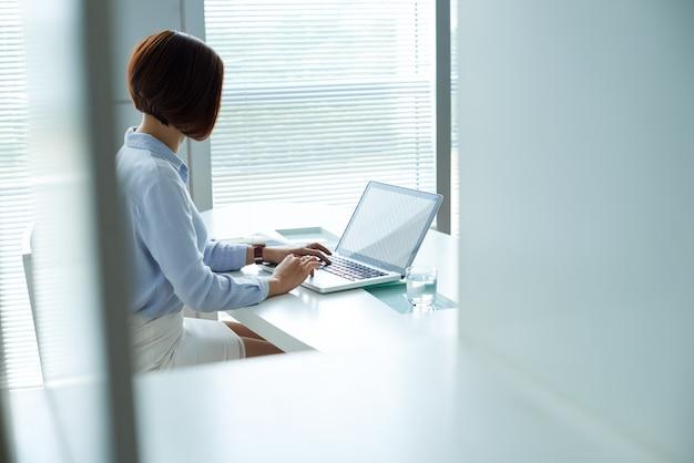 Verkleideter nocken schoss von der geschäftsfrau, die am laptop im büro arbeitet Kostenlose Fotos