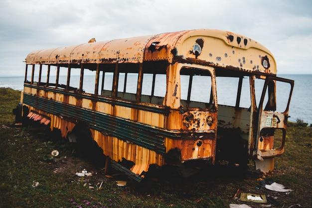 Verlassener gelber bus auf grünem gras nahe gewässern während des tages Kostenlose Fotos