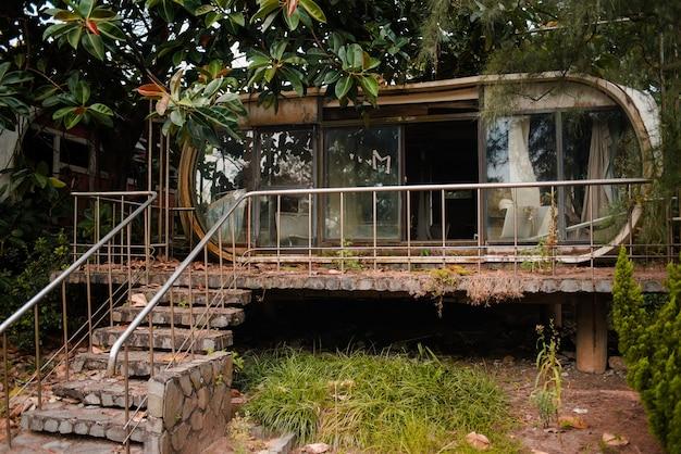 Verlassenes altes gebäude mit glasfenstern in einem garten im wanli ufo-dorf, taiwan Kostenlose Fotos