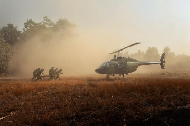 Verletzte soldaten per helikopter zurückschicken. kampfsoldaten, die einen verletzten freund tragen Premium Fotos