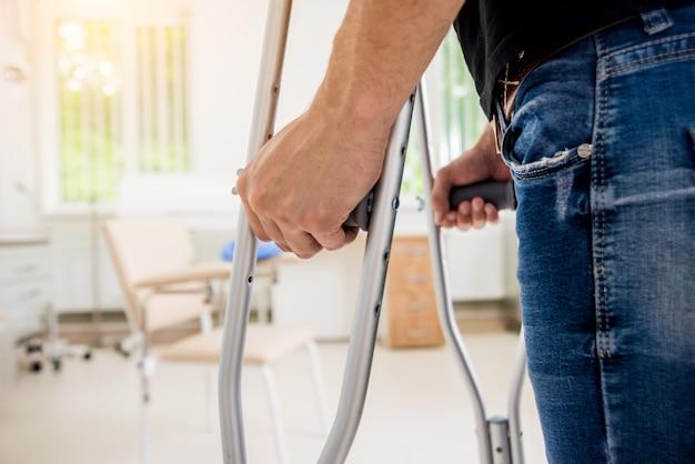 Verletzter mann, der versucht, auf krücken im krankenhaus zu gehen. Premium Fotos