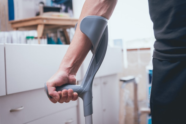 Verletzter mann, der versucht, auf krücken zu gehen. Premium Fotos