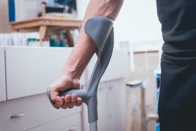 Verletzter mann, der versucht, auf krücken zu gehen Premium Fotos