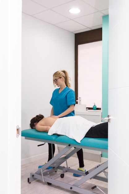 Verletzter patient, der eine therapeutische massage am oberen körperteil erhält Premium Fotos