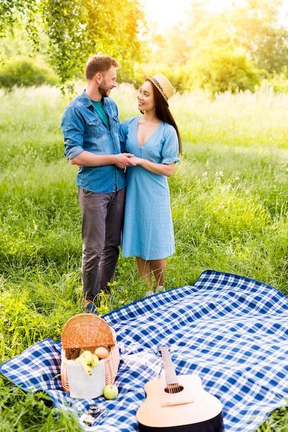 Verliebte paare, die bereitstehendes kariertes plaid auf picknick umarmen Kostenlose Fotos