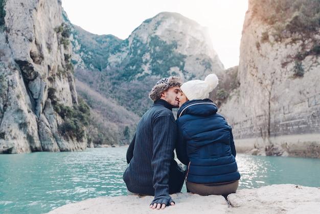 Verliebte paare küssen sich im winter vor einer berglandschaft. konzept über liebe, reisen, menschen und lebensstil Premium Fotos