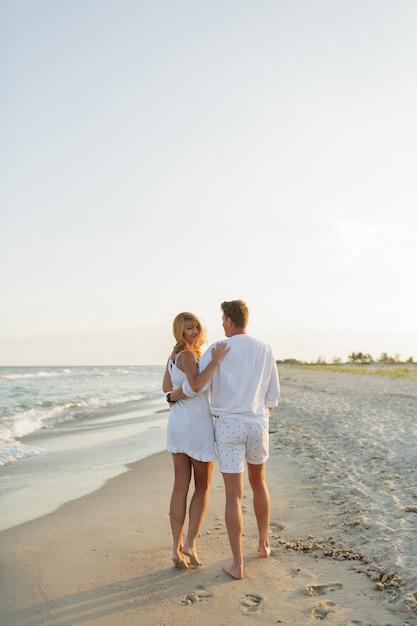 Verliebtes paar in weißen kleidern, die am strand spazieren gehen. volle länge. Kostenlose Fotos