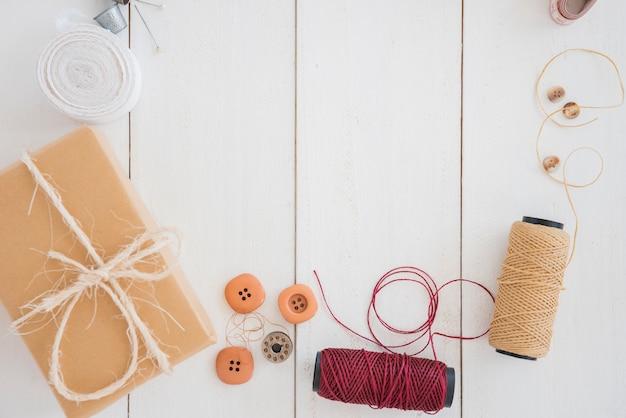 Verpackte geschenkbox; tasten; spule und fingerhut auf weißem schreibtisch aus holz Kostenlose Fotos