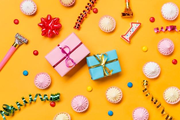 Verpackte geschenkboxen; aalaw; luftschlangen; edelsteine; und verpackte geschenkboxen vor gelbem hintergrund Kostenlose Fotos