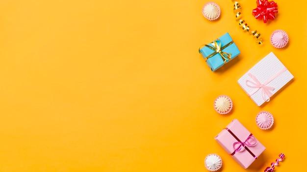 Verpackte geschenkboxen; aalaw; luftschlangen und eingewickelte geschenkkästen auf gelbem hintergrund Kostenlose Fotos