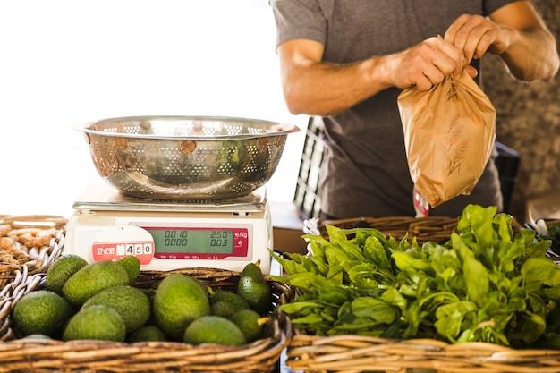 Verpackungsgemüse des männlichen gemüseverkäufers für kunden am markt Kostenlose Fotos