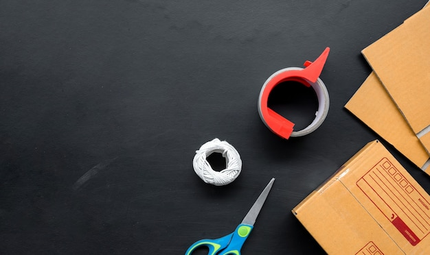 Verpackungszubehör auf schwarzem hölzernem hintergrund. Premium Fotos