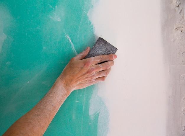 Verputzender mann, der die putzhand in trockenmattennaht schleift Premium Fotos