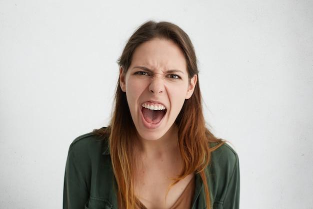 Verrückte kaukasische frau, die laut schreit und ihren mund mit gerunzelter stirn öffnet, mit wut, die ihre negativen gefühle demonstriert. Kostenlose Fotos