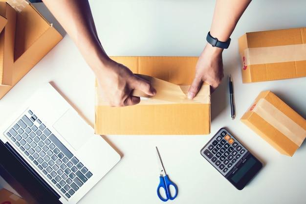 Versand-online-verkäufe. mannarbeitskraft-zustelldienst und arbeitsverpackungskasten, arbeitsprüfungsauftrag des geschäftsinhabers, zum vor dem senden des kunden im beitrag zu bestätigen beschneidungspfad eingeschlossen Premium Fotos