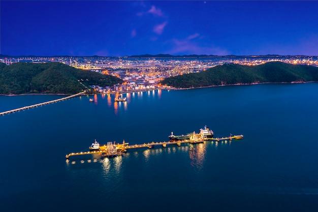 Versandöl und hafenpunktladenöl und petrochemikalie in der see- und raffineriefabrikzone mit hintergrund des blauen himmels nachts Premium Fotos