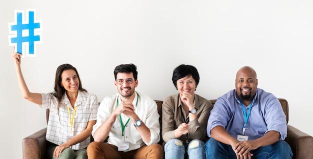 Verschiedene arbeitskräfte, die frau zusammenhalten, die hashtag ikone hält Premium Fotos