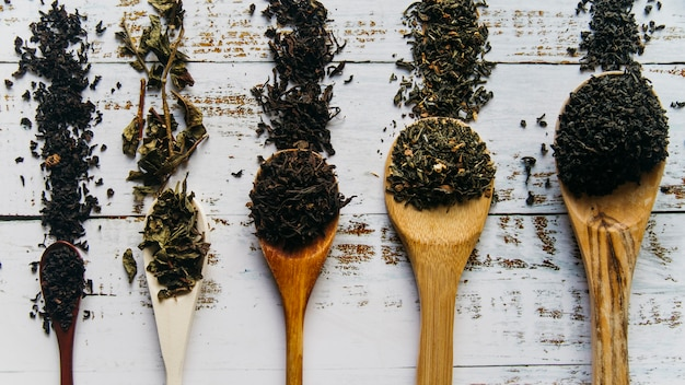 Verschiedene art von teekräutern auf hölzernem löffel über dem weißen hölzernen schreibtisch Kostenlose Fotos
