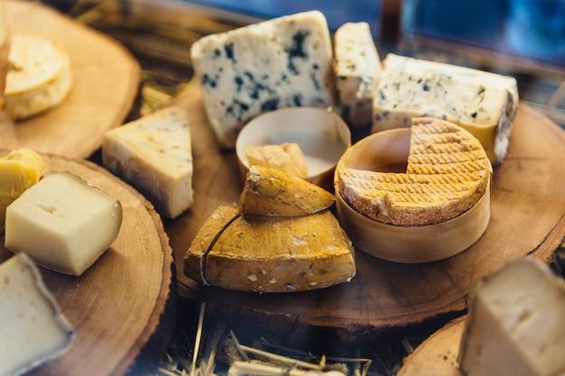 Verschiedene arten des käses auf rustikalem hölzernem hackendem brett. Premium Fotos