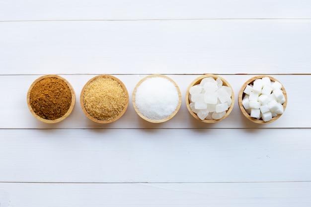 Verschiedene arten des zuckers auf weißem hölzernem Premium Fotos