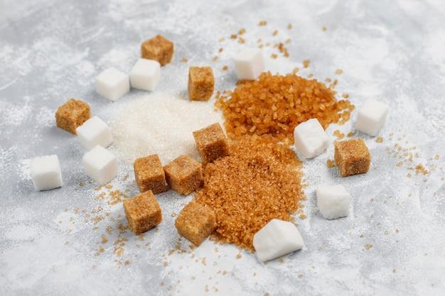 Verschiedene arten des zuckers, des braunen zuckers und des weiß auf konkreter, draufsicht Kostenlose Fotos