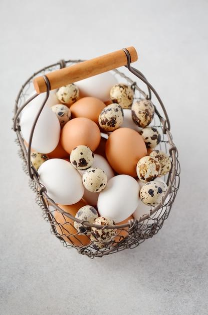 Verschiedene arten von eiern in einem korb auf einem grauen konkreten hintergrund. Premium Fotos