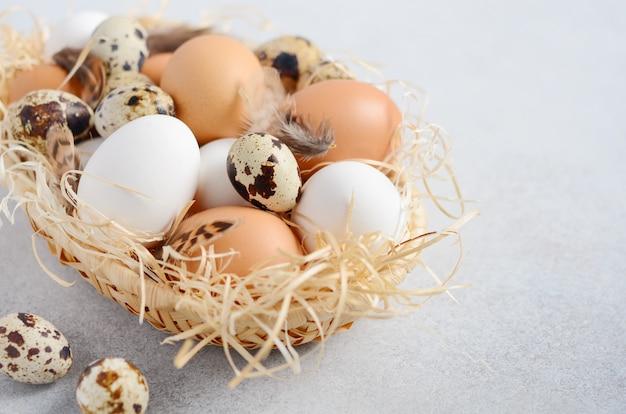 Verschiedene arten von eiern in einem korb auf einer grauen konkreten tabelle Premium Fotos