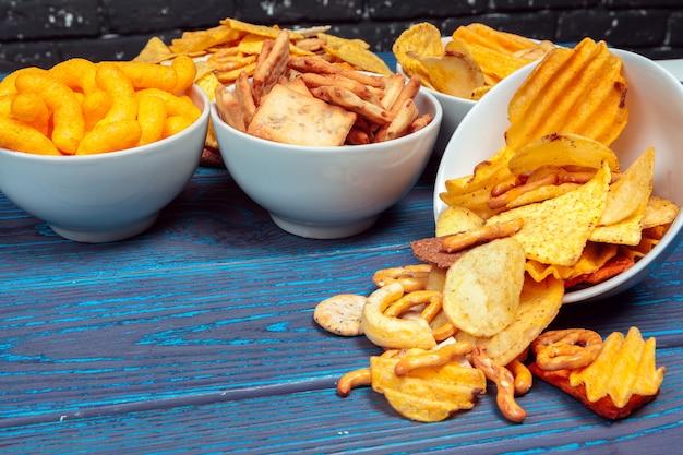 Verschiedene arten von fertigkost, salzstangen, salzcracker auf holztisch Premium Fotos