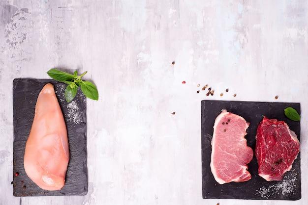 Verschiedene arten von fleisch auf dunklem schieferschneidebrett. schlanke proteine. Premium Fotos