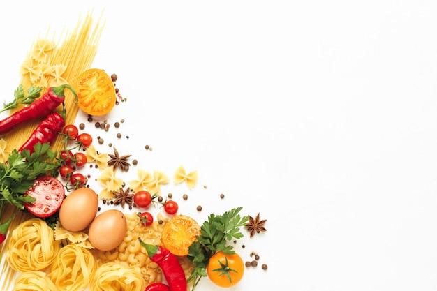 Verschiedene arten von italienischen nudeln, nestern, spaghetti, gewürzen, glühender chilipfeffer, hühnereier, tomaten, kirsche, hellweißer steinhintergrund. flache lage, draufsicht Premium Fotos