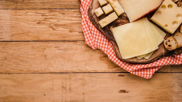 Verschiedene arten von käse auf hölzernem untersetzer mit tischdecke über bank Kostenlose Fotos