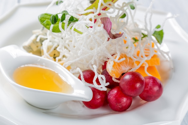 Verschiedene arten von käse mit trauben und walnuss auf weißer platte Premium Fotos
