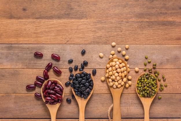 Verschiedene arten von natürlichen bohnen, von rotem, von schwarzem, von grünem und von soja in den löffeln auf holztisch, draufsicht Premium Fotos