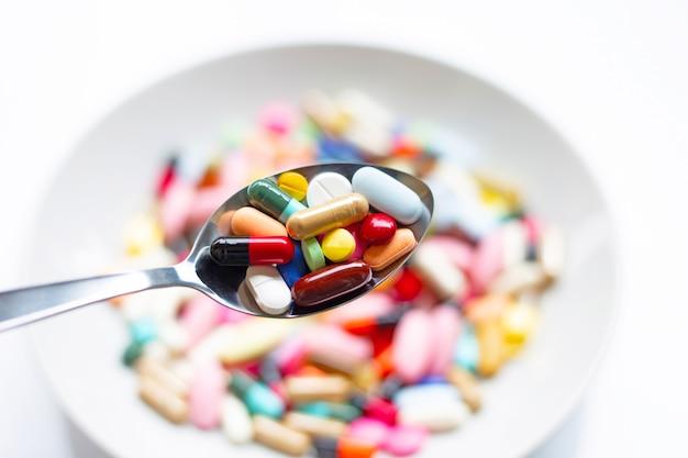 Verschiedene arten von tabletten, kapseln und pillen auf löffel mit bunter medizin. Premium Fotos