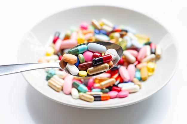 Verschiedene arten von tabletten, kapseln und pillen auf löffel Premium Fotos