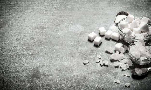 Verschiedene arten von weißzucker in einem glas und löffel. auf einem steinernen hintergrund. Premium Fotos