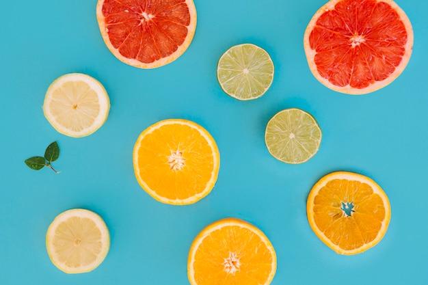 Verschiedene arten von zitrusfrüchten scheiben auf blauem hintergrund Kostenlose Fotos