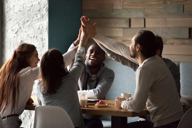 Verschiedene aufgeregte beste freunde, die zusammen hoch fünf bei der cafésitzung geben Kostenlose Fotos