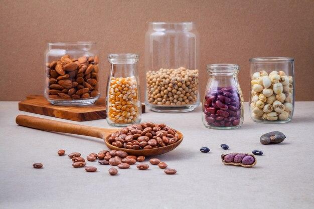 Verschiedene bohnen und nüsse im glas auf braunem hintergrund. Premium Fotos